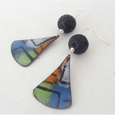 "Torch fired enamel earrings created using the sgraffito technique. Layer upon layer of enamel is sifted onto the copper surface and then I ""scratch"" into the layers of glass powder and torch to create these earrings. Once fired, I have given them an etch bath for a matte finish and combined them with lava rock beads.. Earrings dangle 1 3/4 inches and the earwires are sterling silver with rubber backs."
