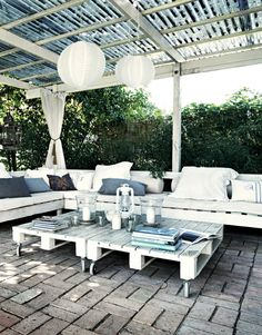 d.i.y. brick deck, recycled material pergola with corrugated metal top, pallet sectional seating & caster wheel pallet coffee tables; white & gray color scheme.