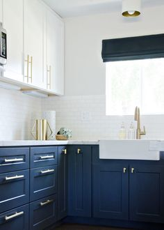 A kitchen remodel featuring navy cabinetry, brass hardware, and farmhouse accents