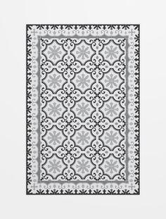 Alfombra que combina un mosaico de baldosa hidráulica tradicional de colores blancos, grises y negros. Alfombra Avenir, de Hidraulik, fabricada en pvc.