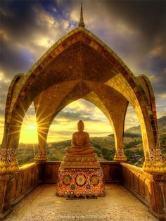 """Sunset behind Buddha sculpture at Wat Phasornkaew, Thailand - a place for meditation that practices """"The Four Foundations of Mindfulness""""."""