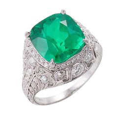 Edwardian domed ring centering an amazing Colombian cushion-shaped, modified brilliant-cut emerald with vivid saturation, in an intricately pierced mounting done in the garland style and set with 45 single-cut, old European-cut and old mine-cut diamonds, approximately 1.45 carats, color: H-I, clarity: VS1-SI2. Circa 1915
