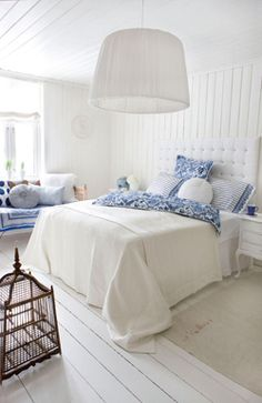 A beautiful white bedroom accented with blue.