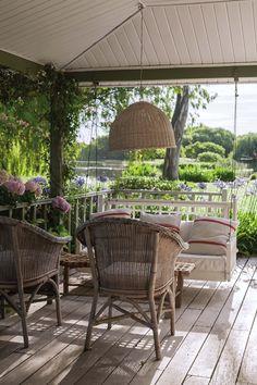 Sillón hamaca y sillones de mimbre blancos en deck que une la residencia con la laguna en una casa de fin de semana en Pilar.