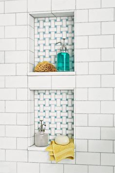 Basketweave tile in updated blue and white marble backing two stacked shower niches set into the subway tile after this luxury bath remodel