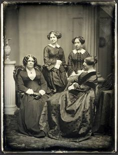 Four unidentified 1850s women (most likely, I'd guess, a mother [woman on left] and her three daughters) posing in lovely dresses for a portrait studio image.