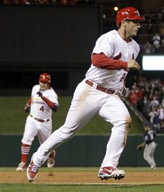 St. Louis Cardinals' David Freese, right, rounds third and heads home to score as Yadier Molina, left, heads to third on a two-run double by Matt Carpenter during the third inning of a baseball game against the Milwaukee Brewers, Friday, April 27, 2012, in St. Louis.