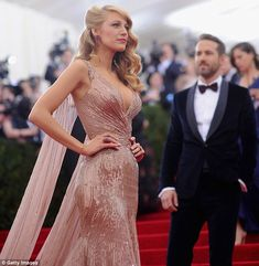 Don't mind me: Ryan looks on as his stunning wife poses for photos at the Metropolitan Mus...