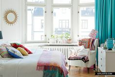 White and turquoise notes. Colorful textiles liven up this Scandinavian style bedroom.