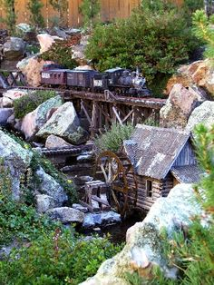 Love the water wheel, the rail structure, the rocks, the landscape - garden railway / railroad