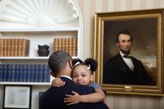 A must-see collection of President Obama's best and funniest candid moments, including adorable photos with kids, playful moments with his family, and other humorous antics.: Obama Hugging a Little Girl