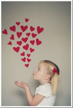 great valentine's day idea  Put hearts on wall and take photo of each kiddo.