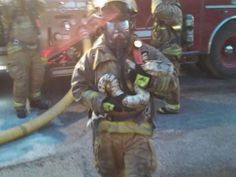 Muskegon, Mich., firefighter Scott Hemmelsbach carries 7-foot boa constrictor to safety from burning house.