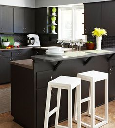 These black cabinets provide the perfect canvas for pops of vibrant colors. See more of this sleek space: http://www.bhg.com/kitchen/color-schemes/inspiration/kitchen-makeover-black-cabinets/