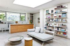 Una casa integrada y moderna  La barra con mesada de Corian y revestimiento de madera recuperada (todo de Skema Revestimientos) da inicio a un recorrido en el que predominará el mobiliario moderno.