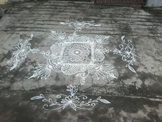 Freehand rangoli in white with peacocks and lotus