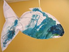 """""""Stuffed Fish"""" via The Artful Parent. Paint large paper fish shapes, glue together (leaving a hole), stuff with recycled paper and hang. These would be fabulous hanging in a group."""