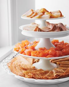 A few stylish touches elevate the presentation. Three cake stands resting on a platter create an etagere for serving smoked fishes (from top: sable, sturgeon, and smoked salmon) and crepes.