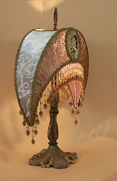 Wonderful Victorian metal lamp base adorned with a dramatic Crescent lampshade with high-quality antique Spanish embroidery with Lilies (that match the Lily motif in the base) in the center circles and 1920s era gold metallic lace on the front panels.  Vintage embossed lavender velvet on the side panels give a luxurious feel to the shade. Custom beaded fringe incorporates all the colors of the shade - lavender, cream, pinks and touches of green.