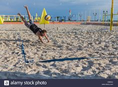 Download this stock image: Young man in motion plays in beach volleyball. - H2BA4J from Alamy's library of millions of high resolution stock photos, illustrations and vectors.