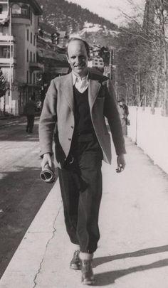 Adam von Trott zu Solz läuft lächelnd, mit einer Zeitung in der Hand, eine Straße entlang.