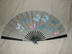 Blue Butterflies. A sheer net fan with appliqued blue and pink silk butterflies which are attached with their bodies allowing the wings to float free.Mounted on antique fan sticks.
