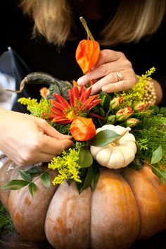 Flowers are arranged in oasis placed on top of pumpkin.