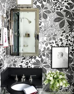 This glamorous Hamptons bathroom has black and white floral wallpaper, black counters, stainless steel medicine cabinet, framed artwork, and colorful hand towels for a pop of color.