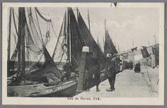 Aan de Haven, Urk 1910-1922 Aan de kade liggen botters met drogende netten in het want. Twee mannen staan op de kade in gesprek met een derde aan boord van de UK 134. Het wasgoed hangt aan de roop (gedraaide waslijn) die is gespannen over de kade. #Urk