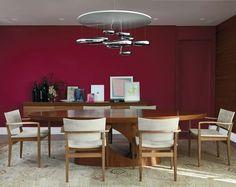 Sala de jantar com mesa oval de madeira + cadeiras de madeira e tecido + pendente moderno cromado + aparador de madeira com quadros apoiados + parede na cor burgundy. Projeto Felipe Alcici, via Casa Cláudia.