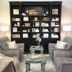 """Jennifer Switz on Instagram: """"After staging my listing last week I was inspired to move a few things around in the sitting room. I'm loving the symmetry! The tripod lamps from @target were my little gift to myself from the staging job.  The shelves hold quite a bit of typography that I would like to share for #itsaspringthing. #mydecormonday #multigrammonday #targetstyle #bookcasestyling #greychairs #goldaccents #tripodlamps #whiteshagrug #bookdesign"""""""