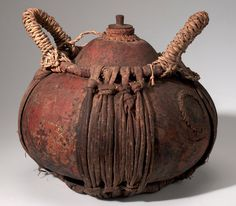 Africa | Vessel with stopper from the Runtu Camp, Okavango Delta, Southwest Africa | Gourd, plant fiber, wood and cord | Possibly Sambu or Mbundu people | ca. 1954