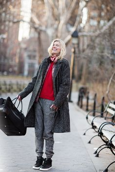 Grey houndstooth coat, red plaid shirt, red sweater, sweatpants, sneakers, black leather weekend bag