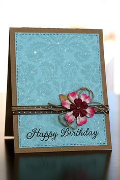 Simple and elegant. Kraft stand-up card with a stitched front panel, wrapped in twine, with a 3-D flower and stamped Happy Birthday.