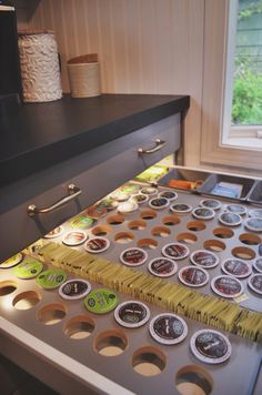 My husband made a lighted coffee drawer with an inset for Keurig coffee pod storage in my IKEA Bodbyn grey kitchen. Chalkboard painted and waxed Karlby walnut countertops, matte white subway tile, silver grout, brass hardware...all DIY!