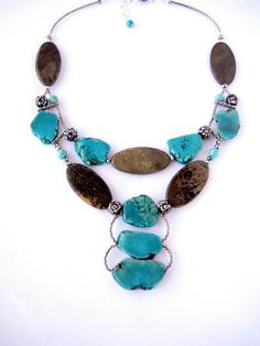 Diversity of shapes, the dynamic contrast in colors of turquoise and river stones combine with rich luxurious silver tone crystals in this intriguing