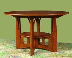 """Limbert Style Table This table has an elliptical top and bent braces, with shelf below. In quarter sawn oak with beechnut brown finish. 30"""" x 48"""" x 30h"""