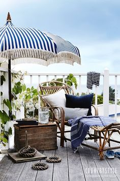A navy and white striped umbrella, rattan chaise, old wooden chest.