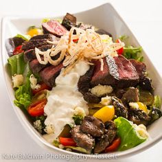 A Lunch Favorite, the Steakhouse Salad. Mesquite grilled prime sirloin steak, wild greens, Rogue River blue cheese, marinated mushrooms, tomatoes, crispy shallots, white balsamic vinaigrette and Roquefort fromage. #johnhowiesteak #lunch #salad