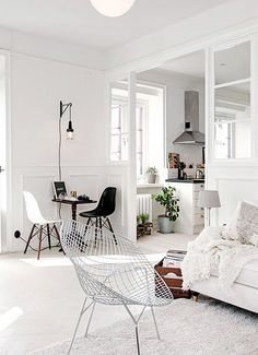 France and son admires the style of this living room. The all white layout with a single black Eiffel chair adds a modern touch.