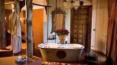 A sexy tub at &Beyond Ngorongoro Crater Lodge in Tanzania, with fresh roses flown in from Arusha--perfect for a safari honeymoon in Africa Estilo Colonial, British Colonial Decor, Restaurants, Bar Restaurant, Game Lodge, Ensuite Bathrooms, Hotel Bathrooms, Master Bathroom, Beaded Chandelier