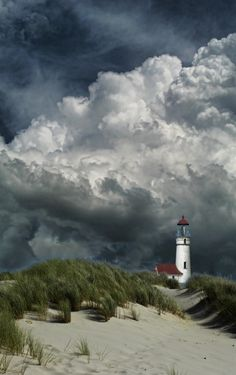 The sturdy lighthouse stands against the dark impending storm.