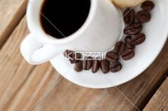 coffee cup and beans - Close-up of coffee cup and coffee beans over wooden surface
