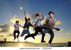 stock photo : Band of young male musicians jumping with instruments against sunset sky background