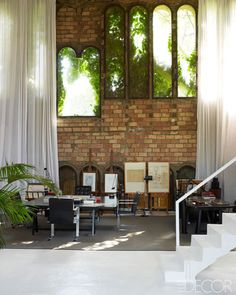 Once an abandoned cement factory, now the home and office of Spanish architect Ricardo Bofill. Loving how the light shines through the greenery beyond the windows.