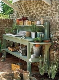 A Potting Bench for the Garden - That lovely shade of green looks fabulous against the beautiful brick wall...hmmmm...a brick wall...I wonder... .