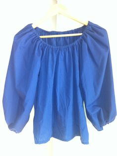 This is a basic Royal Blue Chemise. It is a perfect item for a Women's Renaissance Faire outfit. It is made of Poly/Cotton Blend. It has an elastic collar and cuffs. It is short-waisted and comes in a size Medium. It is made to be sit on the shoulders and is loose in the chest and arm. Which allows for a wide range of motion and movement.