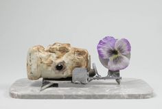 JJ PEET, Machine Gun Lover, 2014; porcelain, aluminum, granite, tape and flower, 5 x 12 x 5 inches.