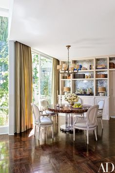 In the dining alcove, a 1940s Empire-style bronze chandelier is suspended above a horn-inlaid Karl Springer table, which Klein inherited from his grandmother; the curtains are made of a Schumacher fabric.