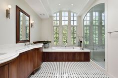 This arched ceiling bathroom in white features rich dark wood cabinetry and bathtub surround over white patterned tile flooring. Glass entry shower stands across from marble topped vanity. Best Bathroom Flooring, Vinyl Tile Flooring, Kitchen Flooring, Kitchen Backsplash, Wall Tiles, White Bathroom, Master Bathroom, Wooden Bathroom, Bathtub Surround